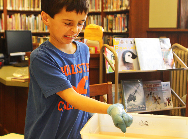 William Pollock, 9, of Manchester, squeezes a homemade blubber substance in his hand at the Manchester Public Library during a hands-on science workshop on Saturday morning. Jesse Poole/Gloucester Daily Times Jan. 7, 2012