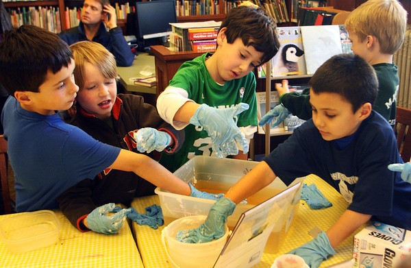 A group of boys enjoy the funny feeling of a synthetic blubber and see how warm it keeps their hands in cold water. This messy experiment was part of a fun hands-on science workshop sponsored by the Manchester Public Library on Saturday morning. Jesse Poole/Gloucester Daily Times Jan. 7, 2012