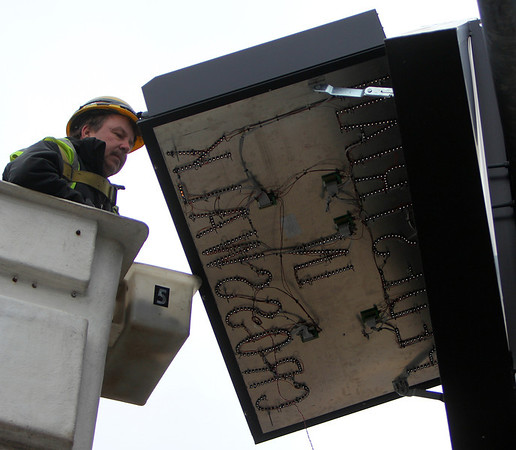 "ALLEGRA BOVERMAN/Staff photo. Gloucester Daily Times. Gloucester: Richie Gallagher of Cobiello Electric of Medford repairs the lettering on the road sign ""Pedestrians in Crosswalk"" that is along the Route 128 Extension on Thursday afternoon."