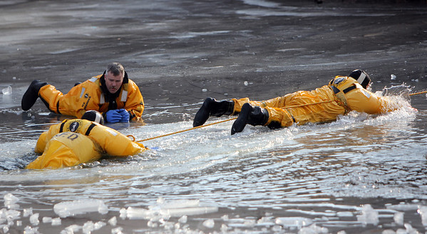 ALLEGRA BOVERMAN/Staff photo. Gloucester Daily Times. Gloucester: Mark McCabe, upper left, technical rescue coordinator of the Massachusetts Fire Academy instructs Gloucester firefighters Greg Marchant and Rob Gerety as they take turns rescuing each other out of a hole in the ice at the pond at Cape Ann Sportsman's Club on Tuesday afternoon.