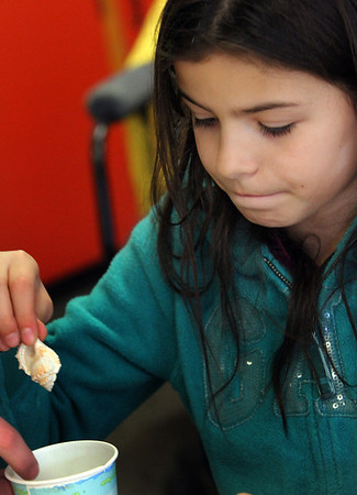 ALLEGRA BOVERMAN/Staff photo. Gloucester Daily Times. Gloucester: The Gloucester Maritime Center works with classes at Veterans Memorial Elementary School from time to time. For the third grade science unit on rocks and minerals and sediment, the pupils learned about how fossils are created and how sedimentary rock are formed. Here, Caroline Oliveira readies a shell that will make its mark on an imaginery sea floor by filling a cup with sand, pressing a shell into the sand, and then covering that layer with plaster, which will harden in a few days and when the cup is dismantled, the sand poured out, a fossil imprint will remain.
