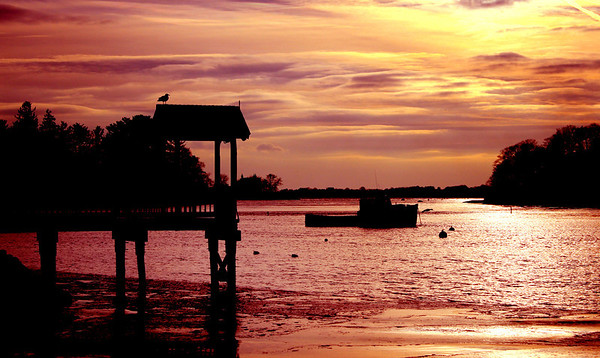 Jim Vaiknoras/ Gloucester Times: The sun set behind a fishing boat off Masconomo Park in Manchester.