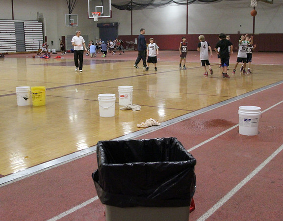 Allegra Boverman/Gloucester Daily Times. The roof in the field house at Gloucester High School is leaking and buckets have been set out around the gymnasium to catch the water. Traveling basketball teams were practicing around them on Wednesday evening.