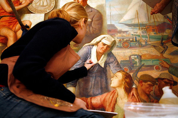 """Allegra Boverman/Gloucester Daily Times. Painting conservator Stephanie Angelo (along with Jackie Trombley and Peter Williams) is restoring the """"City Government"""" mural in Gloucester's City Hall. They work with Peter Williams Museum Services and will be working on several murals in the first floor of the building for the next few weeks."""