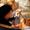 "Allegra Boverman/Gloucester Daily Times. Painting conservator Stephanie Angelo (along with Jackie Trombley and Peter Williams) is restoring the ""City Government"" mural in Gloucester's City Hall. They work with Peter Williams Museum Services and will be working on several murals in the first floor of the building for the next few weeks."