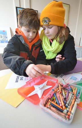 JIm Vaiknoras/Gloucester Daily Times: Sarah Murphy, 13, helps out her brother Michael, 8, as they makes signs that they carried  in the 25th annual Martin Luther King jr march at the Unitarian Universalist Church in Rockport Monday morning.
