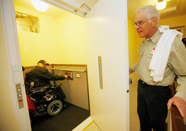 Allegra Boverman/Gloucester Daily Times. Larry Brooks, left, gets into a new lift at the Unitarian Univesalist Church in Gloucester on Wednesday helped by grounds manager Newt Fink, right. Brooks is now able to attend the church functions after not being able to in six years since he's been in a wheelchair. Ceremonies were held at the church to unveil the new lifts and other work in the building that comply with the Americans with Disabilities Act.