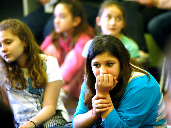 Allegra Boverman/Gloucester Daily Times. During the final assembly at the Gloucester Community Arts Charter School on Wednesday morning. From left, sisters Marisa and Lucia Dimeo listen to their classmates as they shared their favorite memories from being a student at the school.