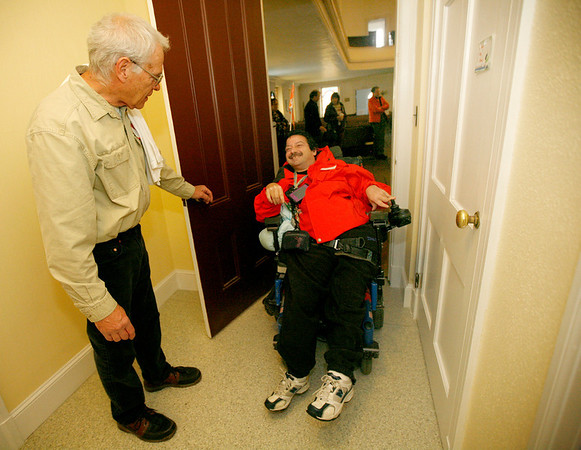 Allegra Boverman/Gloucester Daily Times. During the unveiling of various Americans with Disabilities Act improvements at the Unitarian Universalist Church in Gloucester on Wednesday, Joe Randazza, center, passes through a new door that is now the proper width for ADA standards designed by Newt Fink, left, grounds manager of the church. The door is one that lets out from the church's historic  Meeting House room. The original door opening was only 27 inches wide.
