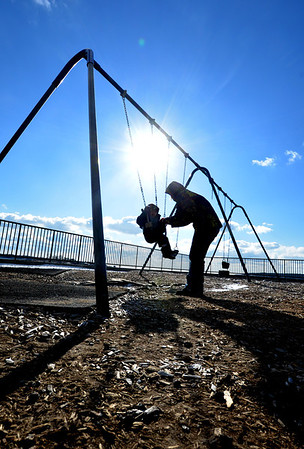 Jim Vaiknoras/Gloucester Daily Time: Jack Fonti, 2, gets a ride on the swings with his mom Hannah at Fort Point Park in Gloucester Tuesday afternoon.