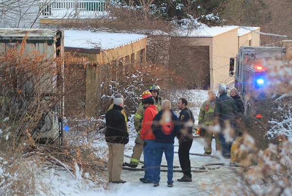 Jim Vaiknoras/Gloucester Times: Emergency personal gather at the scene of a fire at a storage facility on Sargent Street in Gloucester.