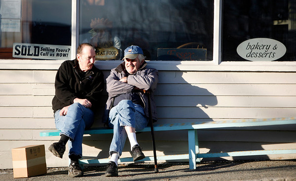 "Allegra Boverman/Gloucester Daily Times. Chatting together in the sun in front of Village Market in Essex on a sunny, mild afternoon Monday are longtime friends Louis Maniates, left, and Floyd Morris, both of Essex. ""You can't ask for a day better than this."" Morris said, of the nice day."