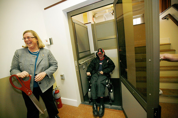 Allegra Boverman/Gloucester Daily Times. Gloucester Mayor Carolyn Kirk, left, cuts a ribbon at one of the new lifts that have been installed in the Unitarian Universalist Church in Gloucester. Church member Larry Brooks, center, is now able to attend the church functions after not being able to in six years since he's been in a wheelchair.  Ceremonies were held at the church on Wednesday for the unveiling of the new Americans with Disabilities Act improvements there.