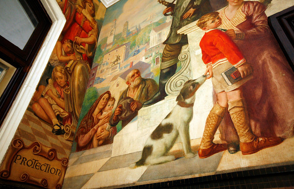 """Allegra Boverman/Gloucester Daily Times. Details of two murals at their juncture that appear in City Hall on the first floor. On the left is """"Civic Virtues,"""" and on the right is """"City Government,"""" both by Charles Allen Winter. They and other murals are being restored for the next few weeks by a team from Peter Williams Museum Services of Boston."""