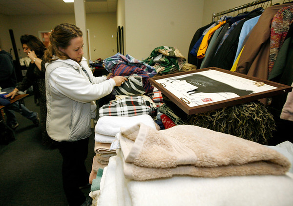 Allegra Boverman/Gloucester Daily Times. City Council member Melissa  Cox folds linens that were donated while Council member Sefatia Romeo Theken, far left, talks with the Second Glance on Wednesday at the Cruiseport room where a clothing and necessities drive was taking place to aid victims of the recent city fires.