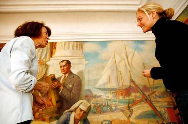 """Allegra Boverman/Gloucester Daily Times. Painting conservators Jackie Trombley, left, and Stephanie Angelo are restoring the """"City Government"""" mural in Gloucester's City Hall. They work with Peter Williams Museum Services and will be working on several murals in the first floor of the building for the next few weeks."""