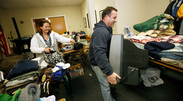 Allegra Boverman/Gloucester Daily Times. City Council member Steve LeBlanc, right, brings in a donated television to the Cruiseport space that is being used for a clothing and necessities drive for victims of several recent fires in the city. Council member Melissa Cox is at left.