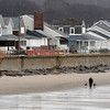 PAUL BILODEAU/Staff photo<br /> <br /> A dog walker strolls along Long Beach in Rockport as temperature returned to above freezing.