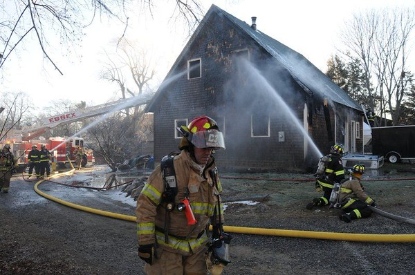 DIMITRA LAVRAKAS/Staff PhotoFiremen hose down hot spots in a barn damaged in a fire on Pickering Street in Essex on Wednesday morning.