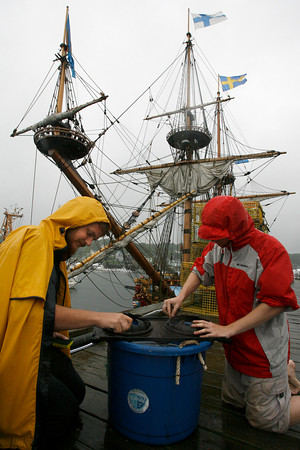 Gloucester: Tucker Cobey, left, and Chris Link, both crewmembers of the Kalmar Nyckel, scrub a stovetop as the ship docked at the Jodrey State Fish Pier yesterday. The ship, which is modeled after a Swedish vessel that crossed the Atlantic in 1638, is headed to Salisbury today for the Merrimack River Maritime Festival this weekend. Photo by Kate Glass/Gloucester Daily Times Tuesday, July 21, 2009