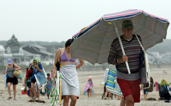 Rockport: Barry Sullivan uses his beach umbrella as a rain umbrella as people leave Long Beach in Rockport after the rain began Friday afternoon. Mary Muckenhoupt/Gloucester Daily Times
