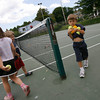 Manchester: Gus Brown, 5, helps gather tennis balls at the end of a lesson at the Brook Street Courts yesterday afternoon. Photo by Kate Glass/Gloucester Daily Times Tuesday, July 14, 2009