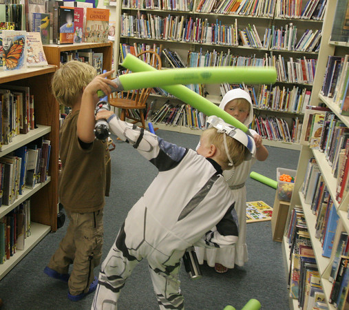 From left to right: Eddie Mulry, 5, Ryan Andrews, 5, as a strom trooper, and Libby Mulry, 3, as Princess Leia, all duel with their lightsabers during the Star Wars Party at the TOHP Burnham Library in Essex. Photo by Maria Uminski/ Gloucester Daily Times