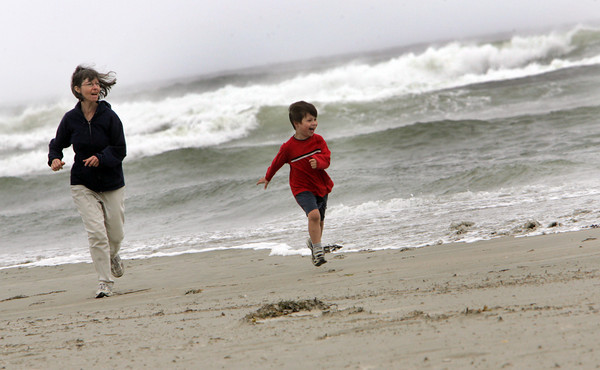Gloucester: Avery Clompus runs awaty from the waves with his mother Hope Green as the tide comes in quickly at Good Harbor Beach Friday.  Avery loved watching the wind and waves come crashing in so his parents took turns taking him down to the water. MAry Muckenhoupt/Gloucester Daily Times