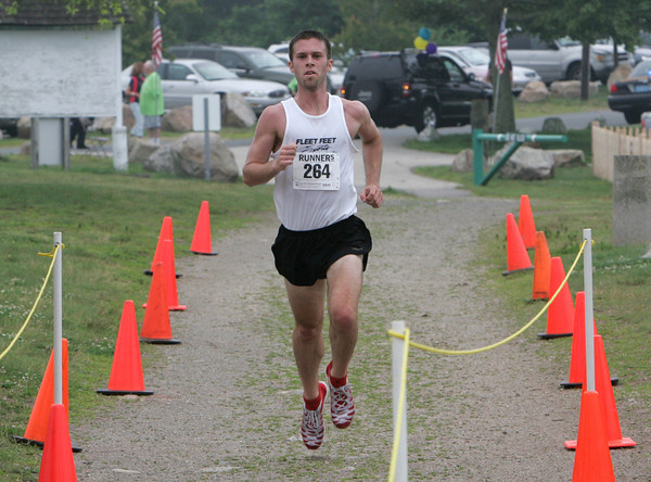Gloucester: Mike Fisher of Brookline is the first to cross the finish line of the sixth annual Seacoast Seven Road Race that began and finished at Stage Fort Park Saturday morning. Photo by Mary Muckenhoupt
