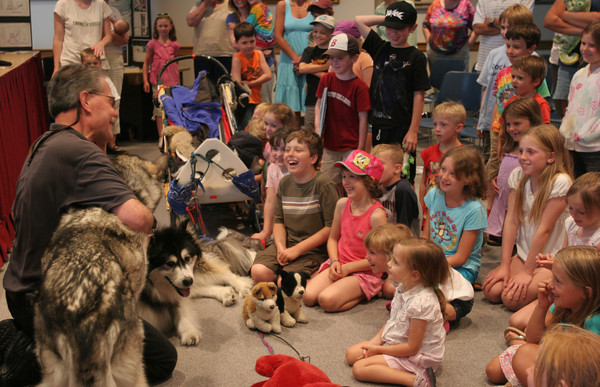 Children at the Rockport Public Library laugh after Su, one of the sled dogs, unexpectedly barked during Harry Schlitz's presentation about  Mountain Mushers, an educational and therapy program that travels across the country. Photo by Maria Uminski/ Gloucester Daily Times
