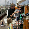 Gloucester: Theron Dodson holds up his son Will, 7, to see the compass of the Corwith Cramer, a 134Õ steel brigantine research vessel owned by the Sea Association of Woods Hole that was docked at the Gloucester Maritime Heritage Center Saturday. The Corwith CramerÕs visit is one of many activities offered at the Heritage Center to provide Gloucester students with hands-on opportunities to learn about marine science.  Mary Muckenhoupt/Gloucester Daily Times