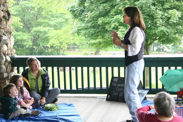 "Gloucester: Alicia Quintano tells a story at Stage Fort Park in the program ""Stories, Songs and More"" as Simon Dickson, 3, Madleen Dickson, 6, and their mom, Heidi Goodwin, are enjoying the fun on Tuesday morning.<br /> Silvie Lockerova/Gloucester Daily Times"