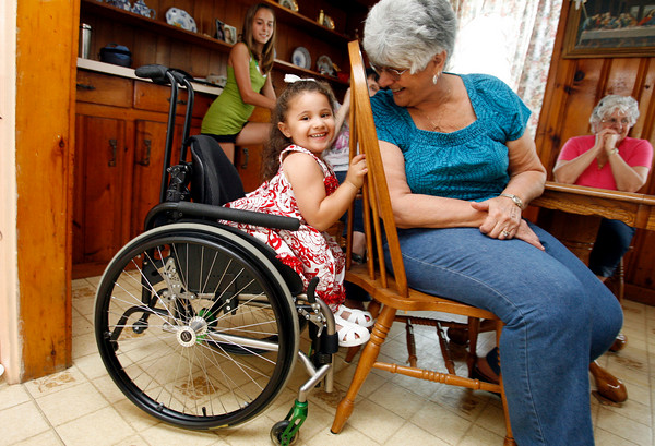 Gloucester: Olivia Curcuru, 3, plays peek-a-boo with her grandmother, Grace Curcuru, while visiting relatives in Gloucester. Olivia, who was born in Gloucester and now lives in Arizona, was paralyzed from the waist down as the result of an accident earlier this year, but refuses to let that slow her down. Photo by Kate Glass/Gloucester Daily Times Monday, July 13, 2009