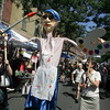 Gloucester: Jessica Parisi, left, and Beth Morris both of the Cape Chamber of Commerce walk down Main Street holding a giant puppet for Cape Ann Art Haven during Gloucester Sidewalk Days Thursday afternoon.  The puppet was made by Yhanna Coffin for SeaArts last year. Mary Muckenhoupt/Gloucester Daily Times