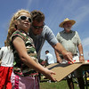 Rockport: Katerina William, 9, holds he cardboard steady as her father Scott makes a straight cut while making thieir boat for the Race to the Bottom boat race, a fundraiser event put on by the Tyrian-Ashler-Acacia Lodge at Back Beach Saturday. Also pictured is Charlie William and Olivia Connelly, right. Mary Muckenhoupt/Gloucester Daily Times