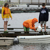 Manchester: Fiona Davis, right, and Calvin Pollard bail out row boats as Nora Pollard and Charlie Davis stand by and wait for their turn at Manchester Harbor by Masconomo Park Friday afternoon.  The group of cousins began bailing out row boats at Tuck's Point when they saw the boats where in danger of sinking before heading downtown to continue their good dead. Mary Muckenhoupt/Gloucester Daily Times