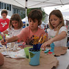 Elizabeth Hanson, 6, Charlie Krupka, 6, and Annie Hendrickson 6, paint figures in an arts and crafts tent during the Cape Ann Farmers' Market yesterday in Gloucester. The three kids are all visiting Rockport for the summer. Photo by Maria Uminski/ Gloucester Daily Times