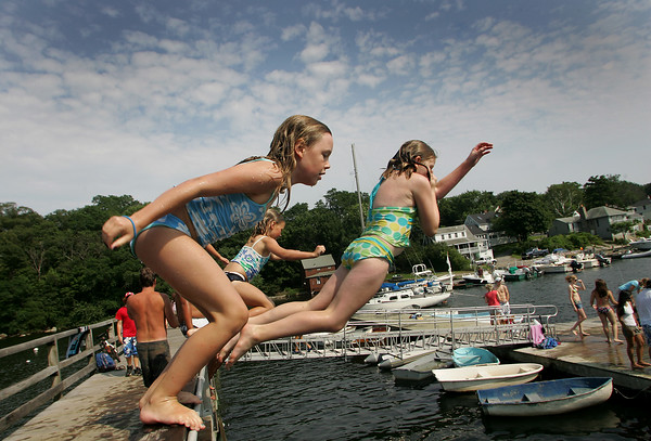 Gloucester: Ava Trotman 9, jumps off the footbridge in Annisquam with Tegan Severance, 11, and her sister Rose Trotma, 7, as the girls cool off Sunday afternoon. Warm, humid weather is expected to continue into the week. Mary Muckenhoupt/Gloucester Daily Times