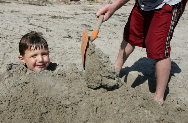 Manchester: Owen O'Leary, 4, of Manchester gets burried up to his neck in sand by his father Gerry at White Beach on Friday afternoon.  Despite all the sand piled on Owen he managed to break free in just a few seconds. Mary Muckenhoupt/Gloucester Daily Times