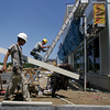 Gloucester: Nelson Sousa carries a piece of siding while working on one of the buildings at the Gloucester Crossing site Friday afternoon.  This builiding will hold three businesses including a Five Guys. Other businesses such as Market Basket, Mashalls and Staples are set to open in August and September. Mary Muckenhoupt/Gloucester Daily Times