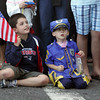 Gloucester: Cole Childers, 8, left, and Liam Burke, 4, wait for the marching band to walk by while sitting on Stacy Boulevard for the Horribles Parade Friday evening. Mary Muckenhoupt/Gloucester Daily Times