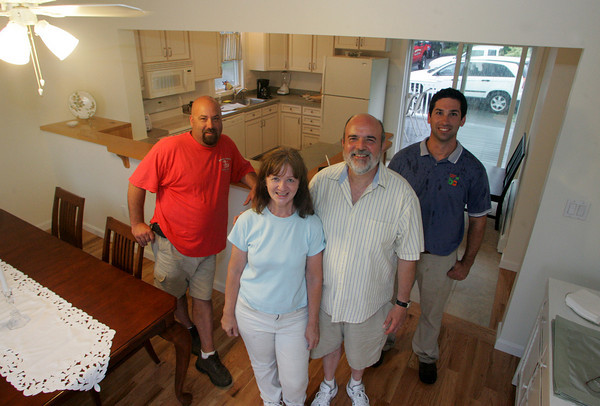Gloucester: JoAnn and Peter Trimmins stand with Darren Collins of Breakwater Construction and Brian Misuraca of the Building Center in their recently rehabiliated homeon Eastern Avenue.  The Trimmons' home was severly damaged after their neighbors home exploded. Mary Muckenhoupt/Gloucester Daily Times