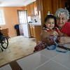 Gloucester: Olivia Curcuru, 3, and her aunt, Mary Parisi, play with sea glass beads as Olivia's mother, Carolyn Curcuru, brings Olivia's wheelchair throught the kitchen. Olivia, who was born in Gloucester and now lives in Arizona, was paralyzed from the waist down as the result of an accident earlier this year, but refuses to let that slow her down. Photo by Kate Glass/Gloucester Daily Times Monday, July 13, 2009