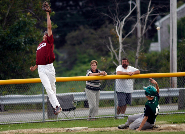 Gloucester: Gloucester's Kellen O'Maley leaps, but cannot come up with the ball as Billerica's Kasey Higgins slides into third during their Senior Little League game at Nate Ross Field last night. Photo by Kate Glass/Gloucester Daily Times Monday, July 20, 2009
