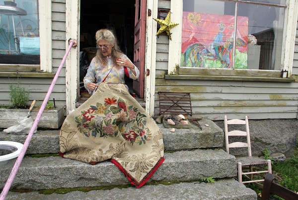 Gloucester: Elizabeth Enfield repairs a hooked rug on the steps of her Washington Street home in Lanesville Thursday afternoon.  Enfield works at repairing and reselling old rugs and thinks this rug is from the 1930's or 1940's. Mary Muckenhoupt/Gloucestr Daily Times