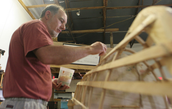 Jim Watson of Gloucester is busy at work waterproofing his double paddled canoe with a coat of polyurethane before moving on to the next step. Watson has been participating in a week-long canoe building class at the Essex Ship Building Museum. Photo by Maria Uminski/ Gloucester Daily Times