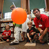 Manchester: George Pechmann of the Museum of Science helps Mawell Kirk, 5, of Manchester launch his balloon rocketship as children learn the science of wind resistance at the Manchester Public Library Thursday afternoon. Mary Muckenhoupt/Gloucester Daily Times