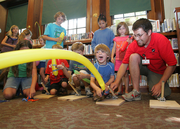 Manchester: George Pechmann of the Museum of Science helps Jagger Nowak, 5, of Manchester launch his balloon rocketship as children learn the science of wind resistance at the Manchester Public Library Thursday afternoon. Mary Muckenhoupt/Gloucester Daily Times