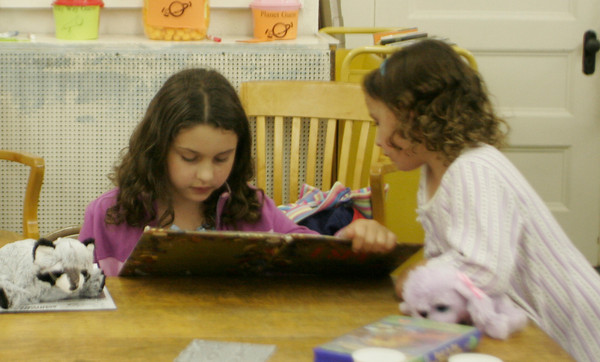 "Sisters Rebecca, 9, and Sarah Braimon, 5, of Essex search through the pages of an ""I SPY"" book during the pajama party last night at the TOHP Burnham Essex library. Maria Uminski/ Gloucester Daily Times"