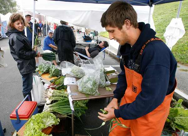 Elise Hansen of Gloucester watches as Noah Kellerman of Alprilla Farm in Essex gathers garlic shoots at their booth at the Cape Ann Farmers' Market yesterday afternoon. Photo by Kate Glass/Gloucester Daily Times Thursday, July 2, 2009